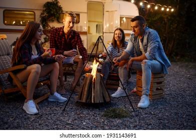 Friends having fun by campfire, picnic at camping