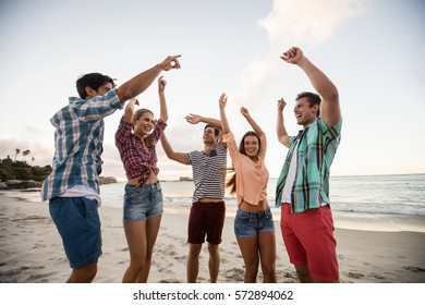 Friends having fun and dancing at the beach