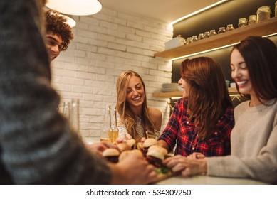 Friends having fun, drinking beer and eating hamburgers.