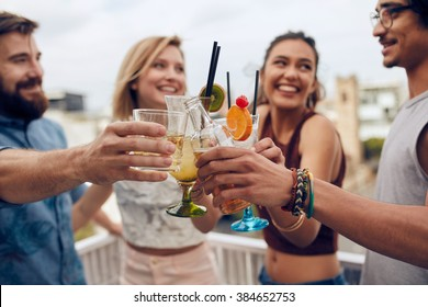 Friends having fun and drinking cocktails outdoor on a rooftop get together. Group of friends hanging out and toasting drinks outdoors. Focus on glasses.