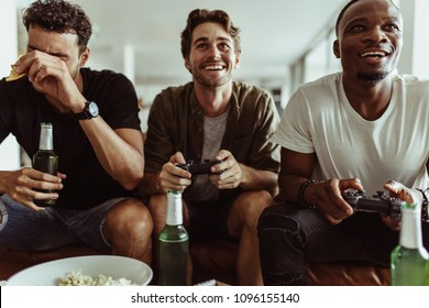 Friends having fun with drinks and snacks while playing video game at home. Two men playing video game holding joysticks while another man watches with a bottle of beer in hand.