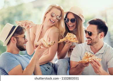 Friends having fun and eating pizza in the city.People,food,friendship and lifestyle concept.
