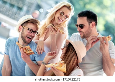 Friends having fun and eating pizza in the city.