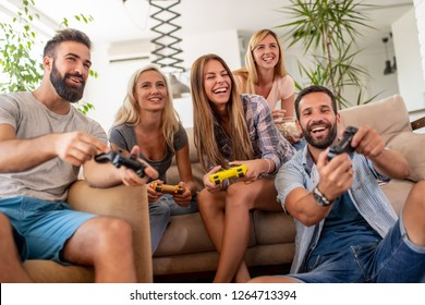 Friends having fun at home,playing video games.