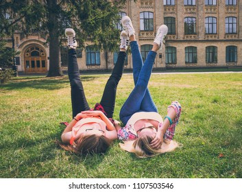 Friends having fun, listening to music and relax in park. Happy teenage girls spend time together in the city