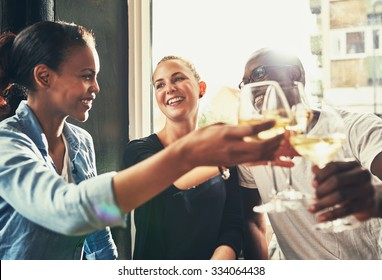 Friends having fun at a local bar while drinking white wine and laughing