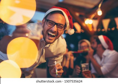 Friends having fun at New Year's Eve party, drinking beer, dancing and blowing party whistles