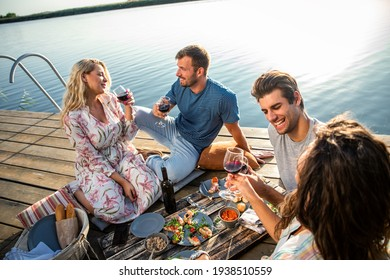 Friends having fun on picnic near a lake, sitting on pier eating and drinking wine.