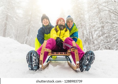 Friends having fun on the snow sliding with a little sled. Girl being pushed by two boys on a sledge. Winter sport and lifestyle,