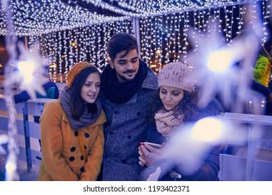Friends Having Fun Outdoors On Winter Market