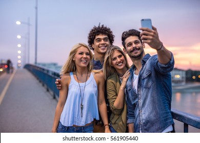 Friends having fun outdoors. Sunset selfie. High ISO, grainy image.