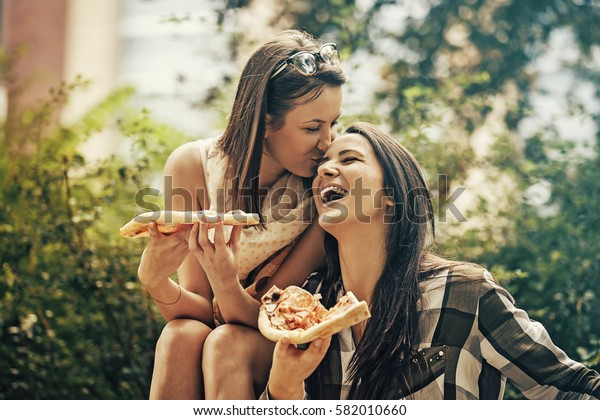 Friends having fun in the park and eating pizza.