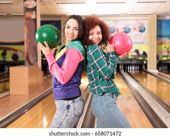Friends having fun and playing bowling