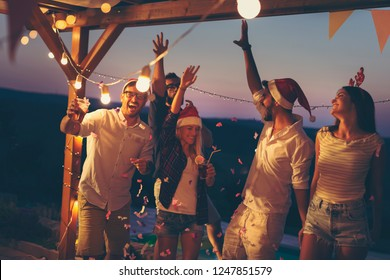 Friends having fun at a poolside New Year's Eve party, dancing and drinking beer. Focus on the guys in the foreground