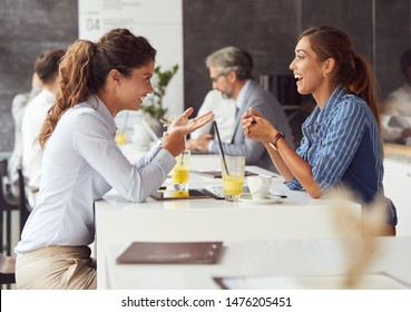 Friends having fun in a restaurant or cafeteria coffee shop. Young business people during a break