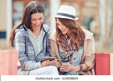 Friends having fun with tablet after shopping.