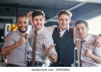 Friends having fun together. Four friends standing arm in arm at the bar and look at the TV and shout loudly and laughing. Friends having fun spending time together