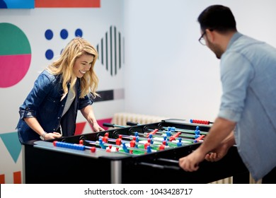Friends having fun together playing table football