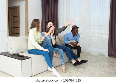 friends having fun together sitting on couch in living room