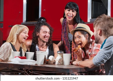Friends having fun while eating pizza outside