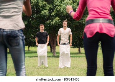 Friends having fun, young men playing sack race in city park with women clapping hands and laughing