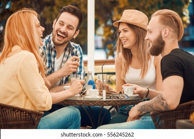 Friends having a great time in cafe.Friends smiling and sitting in a coffee shop, drinking coffee and enjoying together.