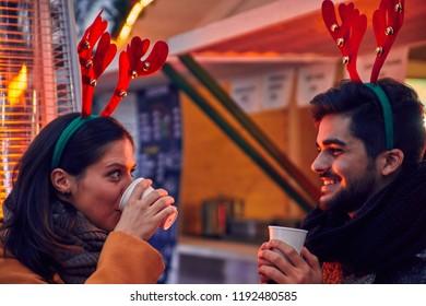 Friends Having Hot Drinks Outdoors On Winter Market