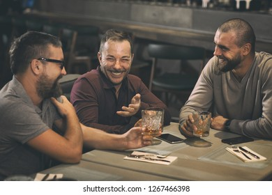 Friends having meeting in bar, having fun and spending time together. Men laughing, communicating while drinking alcoholic beverages. They holding crystal glasses with whisky.