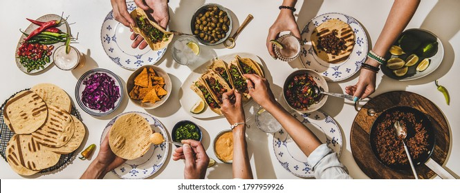Friends having Mexican Taco dinner. Flat-lay of beef tacos, tomato salsa, tortillas, beer, nachos and peoples hands over white table, top view. Mexican cuisine, gathering, feast, comfort food concept