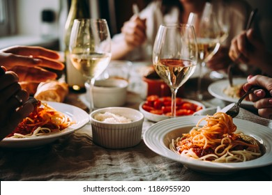 Friends having a pasta dinner at home of at a restaurant.