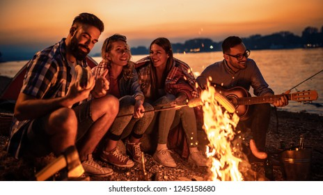 Friends having picnic around the fire.Group of young friends having picnic at night.