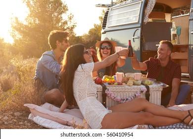 Friends having a picnic beside a camper van making a toast