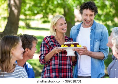 Friends having a picnic with cake in a park