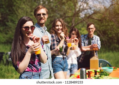 Friends having picnic out on sunny day in park. Elightened company of young people having beverages standing around picnic table out in sun.