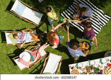 Friends having summer garden party, top view