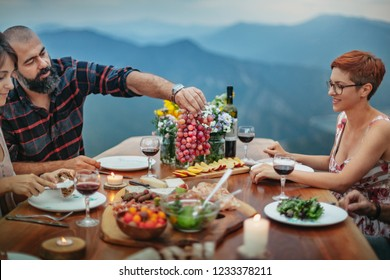 Friends having wine and dinner on a table outside in nature