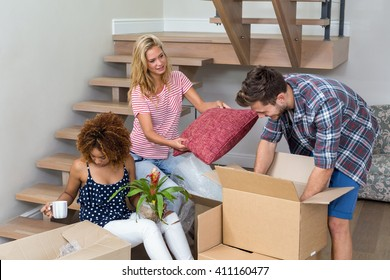Friends helping each other while relocating at new house