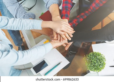 Friends hi-fiving each other at workplace. Teamwork concept. Top view