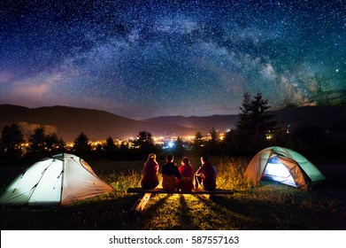 Friends hikers sitting on a bench made of logs and watching fire together beside camp and tents in the night. On the background beautiful starry sky, mountains and luminous town. Rear view