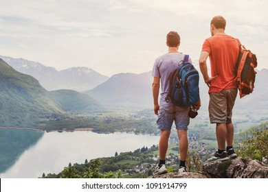 friends hiking in Europe, hike in Alps in Annecy, France, outdoor summer activity with backpack, two people backpackers standing on top of mountain and enjoying beautiful nature landscape background