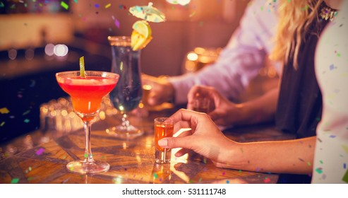Friends holding glass of tequila shot in bar against flying colours
