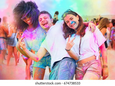 friends at holi party covered with color powder. multi-racial people celebrating spring festival of colors with vibrant red green yellow purple gulal dust.