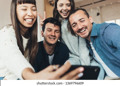 Friends at home party. Four people taking group photo, playing and fooling using mobile phone camera