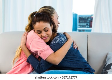 Friends hugging on sofa in living room
