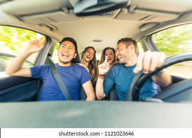Friends inside the car singing during a road trip . Multicultural group of friends leaving for vacations. Two men sitting on the front and two women on the back singing, laughing and having fun
