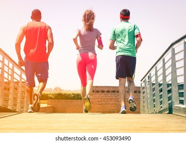 Friends jogging at city park view from back - Multiracial group of runners training outdoor rear scene - Nostalgic concept of healthy lifestyle and leisure activity together - Sun halo focus on shoes
