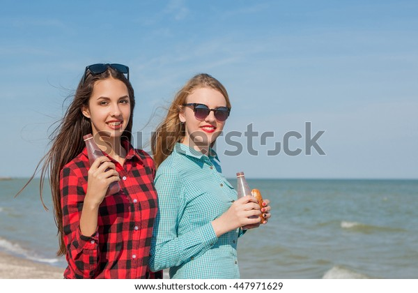 Friends and juice or smoothie. Two young cheerful girls with juice and buns smiling  on background of blue sky