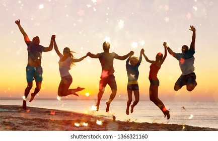 Friends jumping on beach at seaside at sunset