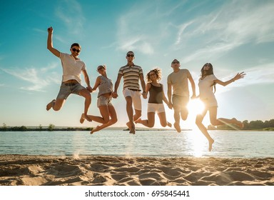 Friends jumping on the beach under sunset sky with clouds at summer sunny day.