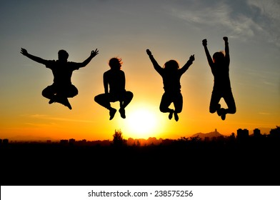 Friends jumping at the sunset